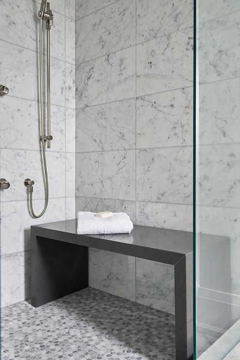 Contemporary bathroom shower is filled with white grid marble .