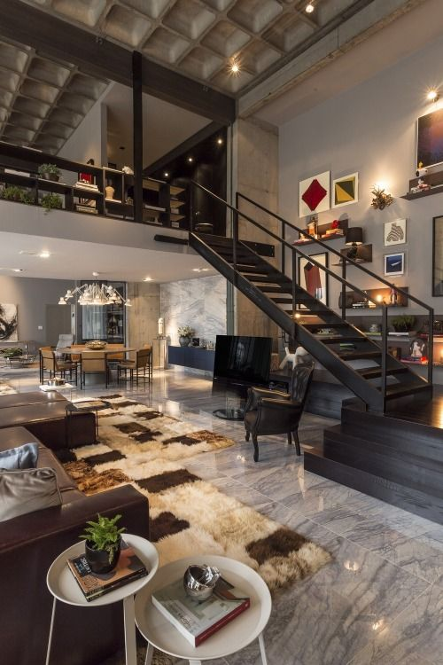 Polished stone floor and double-height ceiling with open loft .