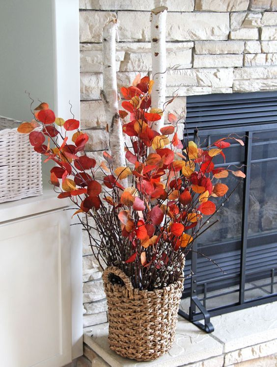 a bold fall decoration of a basket with thick birch branches and .