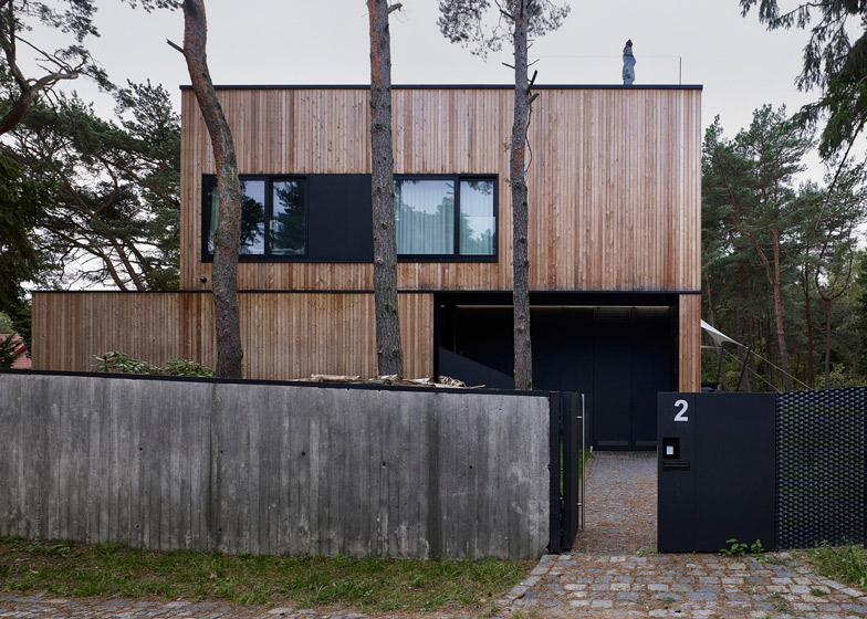Timber-clad house with textured concrete interior by Ultra Architec