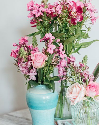 Three different height vases filled with mismatched pink flowers .