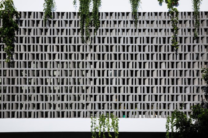 Perforated brick facade shades a house in Vietnam with a triple .