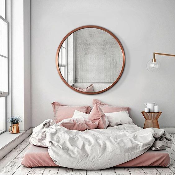 Large round mirror above bed Gold framed round mirror above a desk .