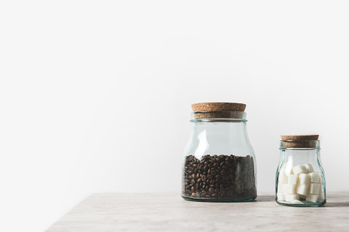 Coffee Beans And Refined Sugar In Glass Bottles On Marble Table On .