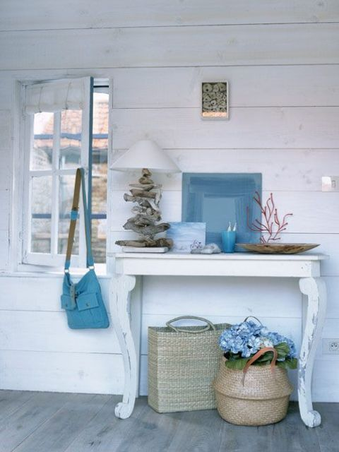 a small console with corals, a driftwood lamp, an abstract artwork .