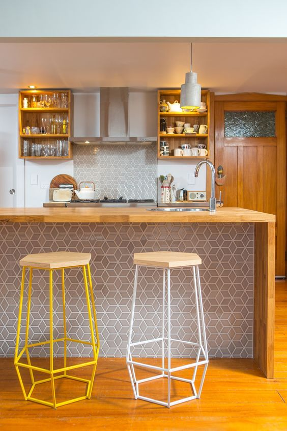 Modern kitchen. A stylish bar counter clad with geo tiles that .