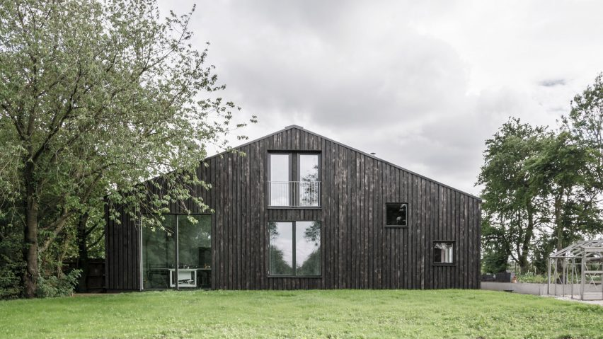 Tractor shed converted into house clad in blow-torch scorched wo