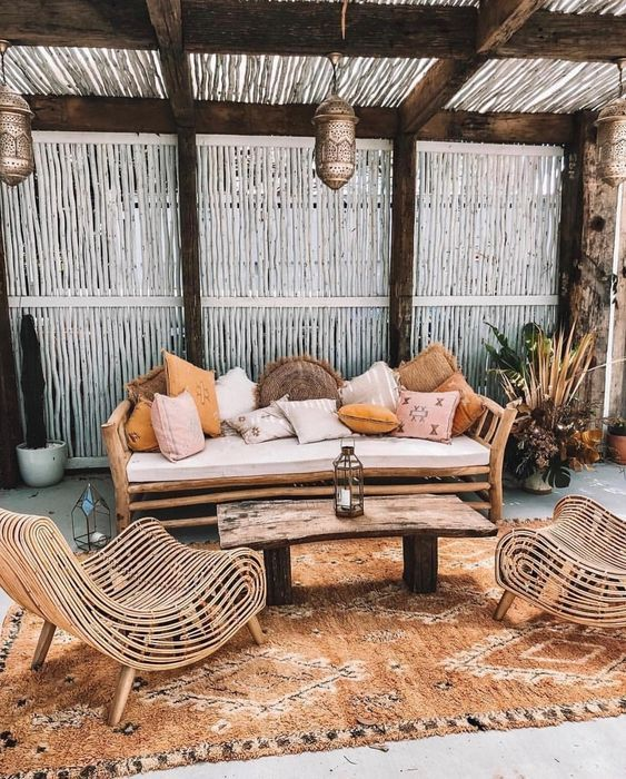 a boho tropical patio with a wooden bench and lots of pillows .