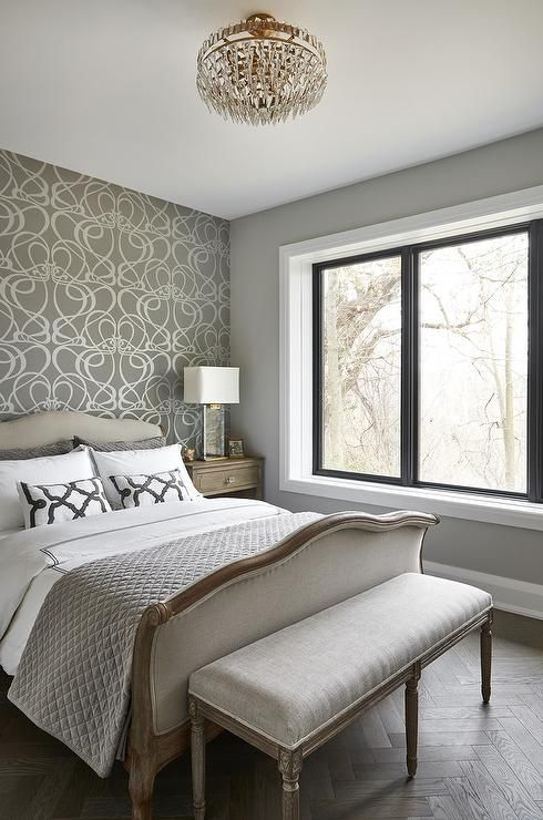 A silver and gray wallpapered accent wall is positioned behind a .